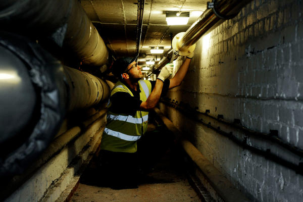 Photo of DLO operative carrying out maintenance to pipework