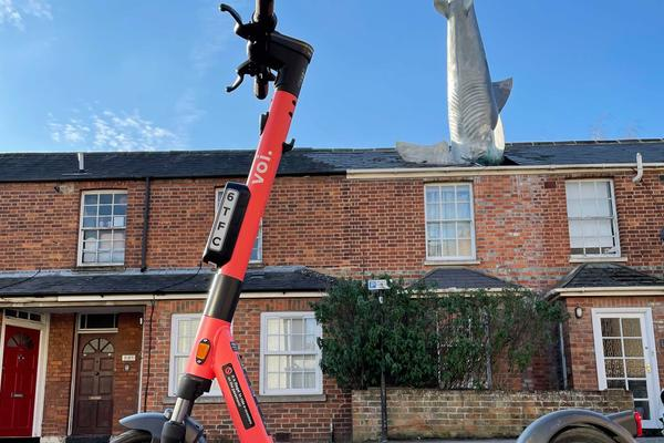 Photo of a Voi-branded red e-scooter parked in front of a house with a shark sculpture in the roof
