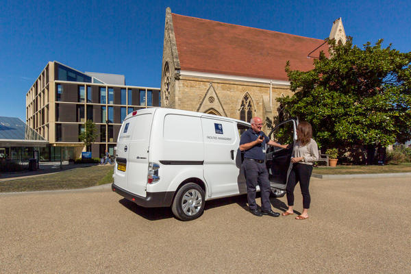 Photo of two FM team members talking in front of the team's new electric van, at the Radcliffe Observatory Quarter.