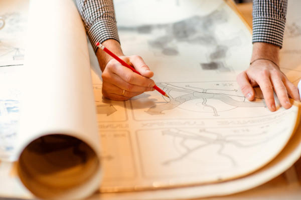 Close up photo of a man drawing on paper town plans with a red pencil