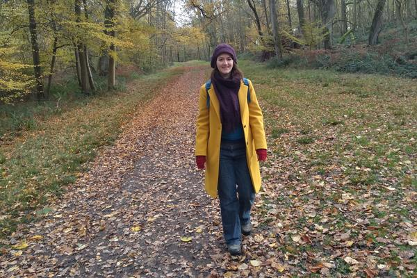 Photo of Alice Little standing in a woodland surrounded by autumn leaves