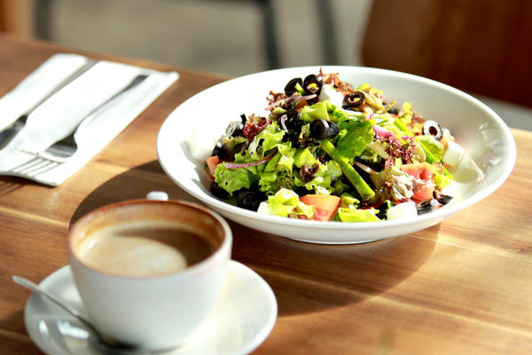 Photo of salad in a bowl and a cup of coffee on a table