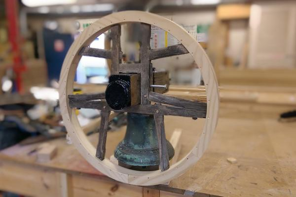Photo of a bell and yoke being restored in a joinery workshop