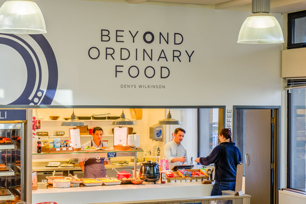 Photo of a cafe with 'Beyond Ordinary Food' text and logo on a white wall above the serving hatch