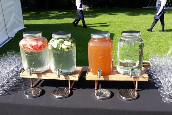 Photo of four glass water decanters on a table with various soft drinks inside