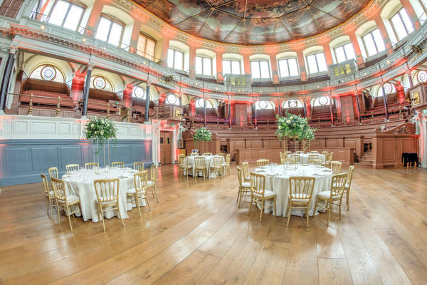 Photo of the Sheldonian Theatre interior set up for a formal dinner, with chairs around round tables