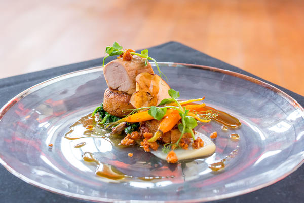 Photo of a beautifully presented roast pork dish on a large plate