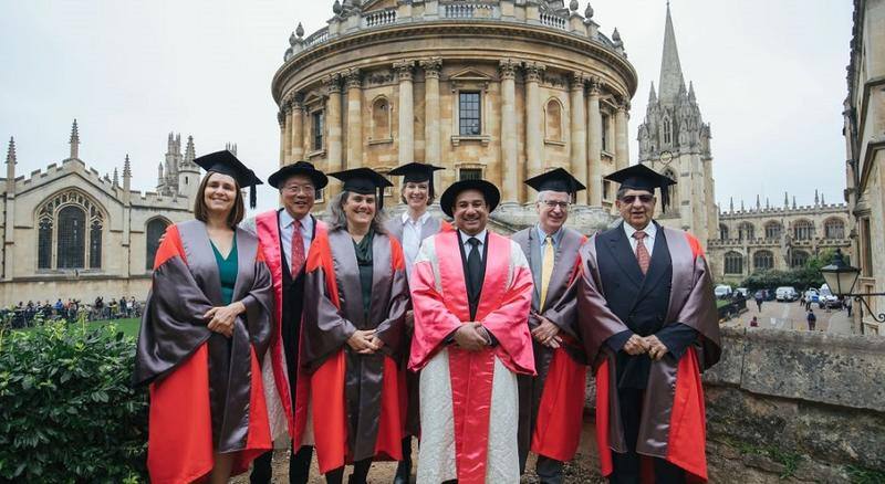 Photo of a group of people in academic dress posing outside of the Sheldonian as part of Encaenia 2019