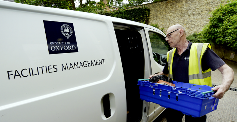 Photo of a man in a high-vis jacket putting a blue crate into a white van with the University of Oxford logo and 'Facilities Management' written on the side