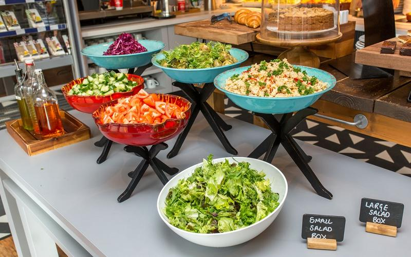 Photo of assorted salads in coloured bowls on a table