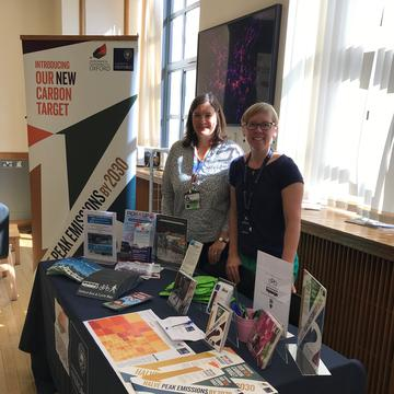Members of the Sustainability team standing behind a table at the Sustainability roadshow