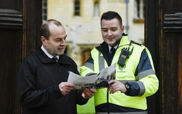 Photo of a male security officer wearing a high-vis jacket looking at a brochue with a male college porter