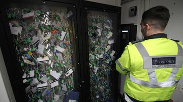 Photo of a man wearing Security Services hi-vis jacket looking at a cabinet full of many different keys and access cards