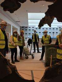 Photo of six people in high-vis jackets, helmets and face masks, looking through a hole in plasterboard towards the camera.