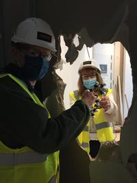 Photo of two people high-vis jackets, helmets and face masks, standing on either side of plasterboard wall and passing a molecular model through a hole in the middle.